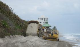 A construction worker dumps sand at Red Reef Park in Boca Raton.  The dunes were badly damaged when Hurricane Sandy brushed South Florida as a tropical storm.