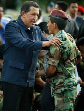 Venezuelan President Hugo Chavez, left, speaks with National Guard Cpl. Juan Rodriguez in Maracay, Venezuela, Sunday, April, 14, 2002.