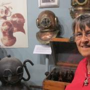Dr. Sally Bauer to the right of the first diving helmet her late husband bought in the 1970s.