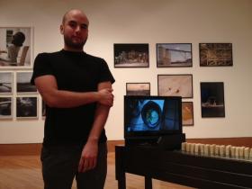 Orestes De La Paz stands by his exhibit, Making Soap, at the Frost Art Museum.