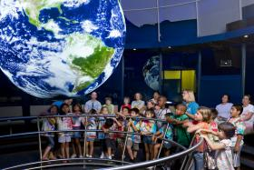 Students look at Science on a Sphere, one of the new exhibitions at the South Florida Science Museum.