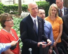Gov. Rick Scott signs the 2013-14 state budget. He told reporters he vetoed a tuition hike because it will help Florida families.