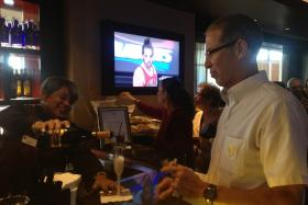 A theater patron enjoys a drink inside Club Level at the Broward Center while a Miami Heat game plays on one of the lounge's two flat-screen TVs.
