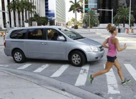 A pedestrian walk across the crosswalk as a vehicle makes a right turn heading west on SW 13 Street in Miami's Brickell area on Wednesday, May 30, 2012.
