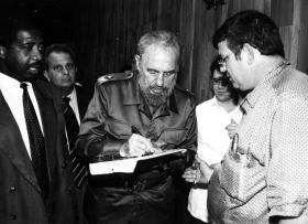 Fidel Castro signs a photo for Patrick Manteiga. The photo he's signing is a shot of Manteiga's grandfather giving Castro money for the revolution.