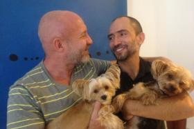 "Julian Marsh (left) and his husband, Traian ""Tray"" Popov (right) with their two Yorkies, Phoebe and Rosie. The two men are the first binational same-sex couple to have a marriage-based green card petition approved by U.S. Immigration officials."