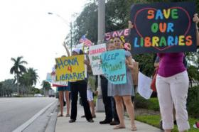 Miami-Dade library supporters rally against potential budget cuts that threaten to close down 22 branches on Saturday, July 27, 2013, outside the Concord Branch Library.