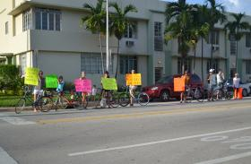 Cyclists hold signs and line 16th Street in Miami Beach.