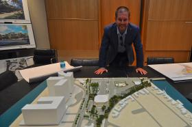 Bal Harbour Shops' Matthew Whitman Lazenby stands above the model of the planned expansion of the shopping center.