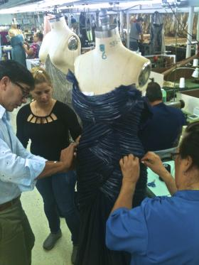Designer Rene Ruiz (left) instructs workers on the finer points of dress making.