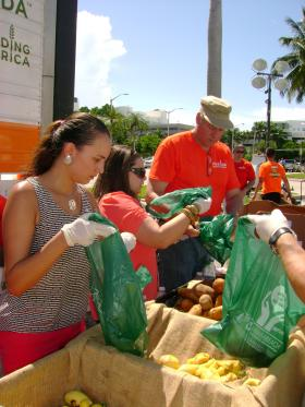 Volunteers hand help hand out food at an event in South Beach for Hunger Action Month.