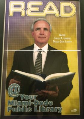 The main branch of the Miami-Dade Public Library features a poster of Mayor Carlos Gimenez.
