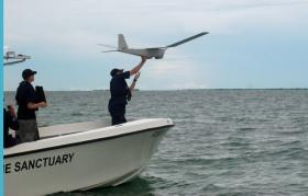 Lt. j.g. Kyle Salling launches an unmanned aircraft that NOAA is testing for science purposes in the Florida Keys National Marine Sanctuary.