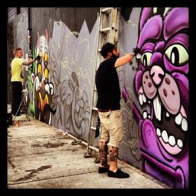 Street artist work on murals in Miami's Wynwood Art District.
