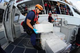Crew members aboard the U.S. Coast Guard cutter Valiant transfer bales of cocaine caught on Feb. 19. Roughly 1,400 pounds of cocaine were seized from a speedboat in the Caribbean in the operation. Officials say drug traffickers are sending larger shipments of cocaine through the Caribbean.