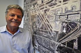 Broward County Aviation CFO Doug Wolfe stands in front of a date ariel photograph of Ft. Lauderdale-Hollywood International Airport. The $2.3 billion expansion project is building a new south runway in addition to a terminal, concourse and other improvements.