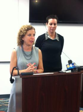 South Florida Congresswoman Debbie Wasserman Schultz (left) speaks Monday at the Fort Lauderdale-Holllywood International Airport, accompanied by Carolyn Newman, a breast cancer survivor who says she will save $7,000 a year on her health insurance plan thanks to the Affordable Care Act.