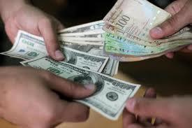 U.S. dollars and Venezuelan bolivares being exchanged in Caracas.