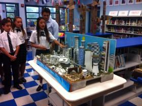 A seventh grade student from St. Thomas the Apostle School shows visitors a tabletop city model constructed by last year's Future City team.