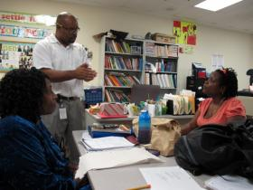 Uzelea Evans, right, and Cynthia Williams, left, talk with GED teacher Travis McGinnis at Metropolitan Ministries. The GED is changing in January, and McGinnis said his students have been planning since September whether to take the old test or the new GED.