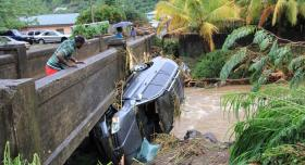 A man in St. Vincent and the Grenadines inspects an SUV washed away in flooding and landslides on Christmas Eve