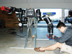 Yong Lin works on RoboSimian, the entry of NASA's Jet Propulsion Labs, before the Robotics Challenge Trials begin at Homestead-Miami Speedway.