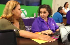 ALMOST DONE: Navigator Nini Hadwen, right, helps an insurance  seeker during a sign-up event at Dadeland Mall.