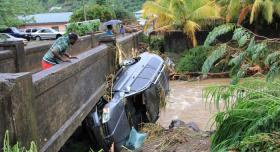 A man in St. Vincent and the Grenadines inspects an SUV washed away in Christmas Eve flooding.