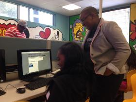 Felecia Hatcher helps a student write an HTML code.