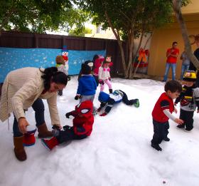 Despite - or perhaps because of - the warm weather, a group of 2- to 3-year-olds enjoy the snow at a preschool in Little Havana.