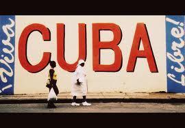 Cuban women walk by wall graffiti in Havana.