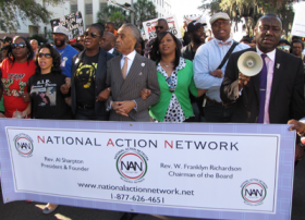 Rev. Al Sharpton (center) marches with parents and family of Trayvon Martin, Jordan Davis and others in Tallahassee Monday. They are calling on Florida to repeal the state's Stand Your Ground law.