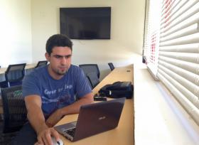 Abel Fernandez, broadcast media junior, using FIU's new Media Innovation Incubator Lab at the north campus. Most of the sea-level rise project meetings will take place here. Students have swiveling desks and chairs, 20 laptops, 20 tablets, a smart TV and a view of the campus.