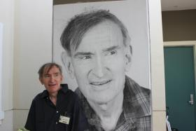 Tom Chiappetta standing next to his potrait at the Miramar Multi-Service Complex.