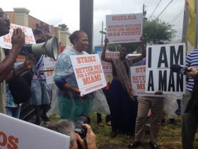 """Fast-food workers hold up signs emblazoned with messages like """"Better Pay for a Stronger Miami"""" to raise awareness for minimum wage increase."""