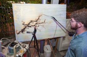 Cory Hunter, an electro-fractal artist from Miami, uses electricity to create branching patterns on a cardboard canvas.