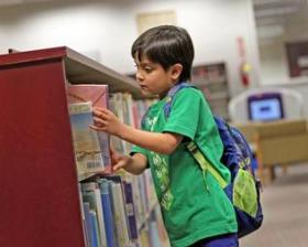 A child looks at books in the West Kendall Library.