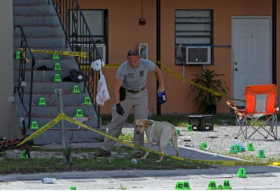 A law enforcement agent and his dog search for evidence at the scene of a shooting in the 6500 block of Northwest 12th Avenue in Liberty City.