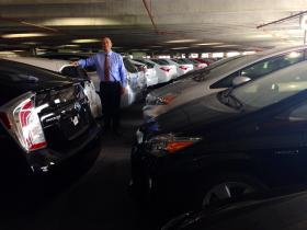 Michael Cordero, fleet manager at Kendall Toyota, stands among dozens of new Toyota Priuses.