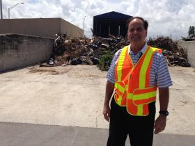 "Alex Perez stands before a massive pile of ""ditch maintenance debris."" Perez, an engineer with FDOT, oversees maintenance for northern Miami-Dade County."