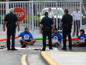 Nestor Ruiz, 21, (second from left) talks to BSO deputies preparing to arrest him and six other protesters outside the Broward Transitional Center.