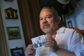 Pedro Fournier holding a picture of himself in Cuba.