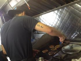 Velasquez cooks burgers in preparation for the lunchtime rush.