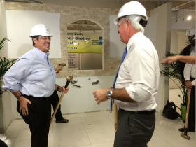 "Jose ""Pepe"" Diaz, left, and Miami-Dade County Mayor Carlos Gimenez take turns breaking down a wall, kicking off the construction of the new shelter"