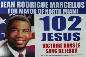 "North Miami mayoral candidate Jean Rodrigue Marcellus declares ""Victory in the blood of Jesus"" on a flier being handed out to voters on election day."
