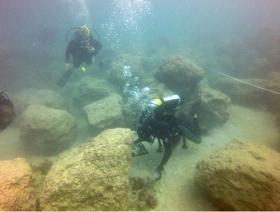 Divers inspect boulders dropped near the channel coral. They were intended to allow new coral to grow, but inspectors found many crushed existing coral.