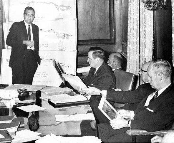 Gov. Farris Bryant and his cabinet members listen to engineer Reginald Waters in a meeting at the Capitol office. Chart shows the proposed improvement Dade County has in mind for the offshore city of Islandia and the submerged land in the area. (1961)