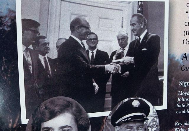 A sign at Biscayne National Park shows a photo of younger Lloyd Miller shaking President Lyndon B. Johnson's hand.
