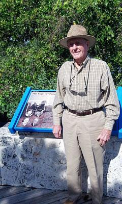 Environmentalist Lloyd Miller stands in front of a sign that shows a picture of himself at Biscayne National Park.