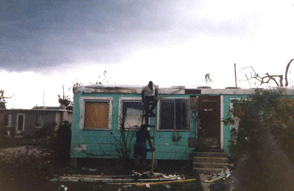 Men work on a home damaged by Hurricane Andrew.